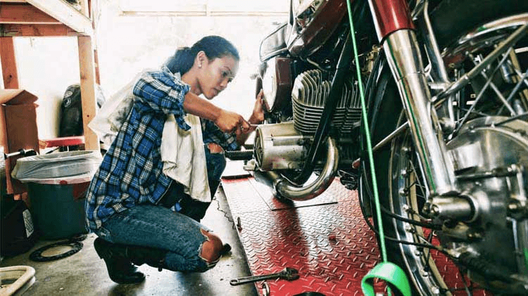 Woman working on a motorcycle in a garage