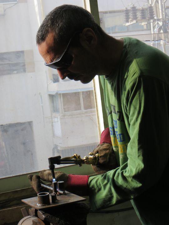 רמי אטר, פסל,  עובד בחום באמצעות מבער, אחד הכלים לנפחות מודרנית.
