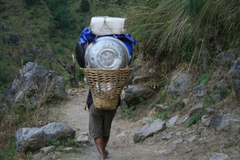 A KITCHEN PORTER HEADS FOR THE NEXT CAMP.