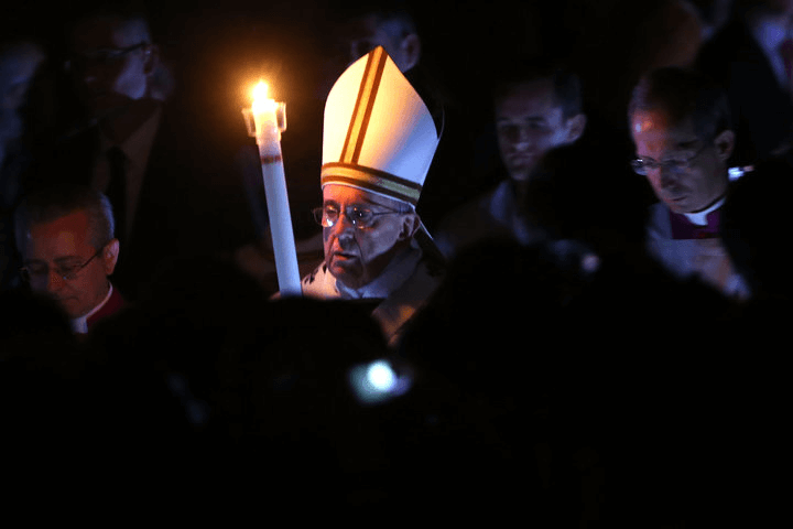 Pope Francis holds the Paschal candle as he arrives at St. Peter's Basilica for the Easter vigil mass on April 4, 2015 in Vat