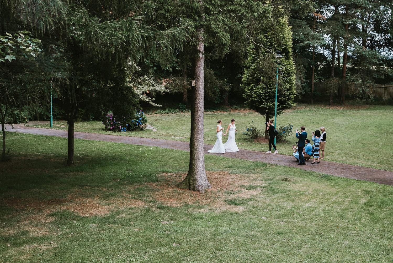 A lesbian wedding couple in a park.