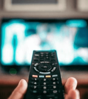 Close-up of remote control pointed at blurred TV screen in background