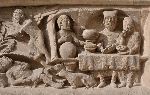 Lazare dont les pustules sont léchées par les chiens, portail de l'abbatiale de Moissac (vers 1120), Tarn-et-Garonne. La même scène est représentée dans un  vitrail de la cathédrale de Bourges (voir agrandissement).