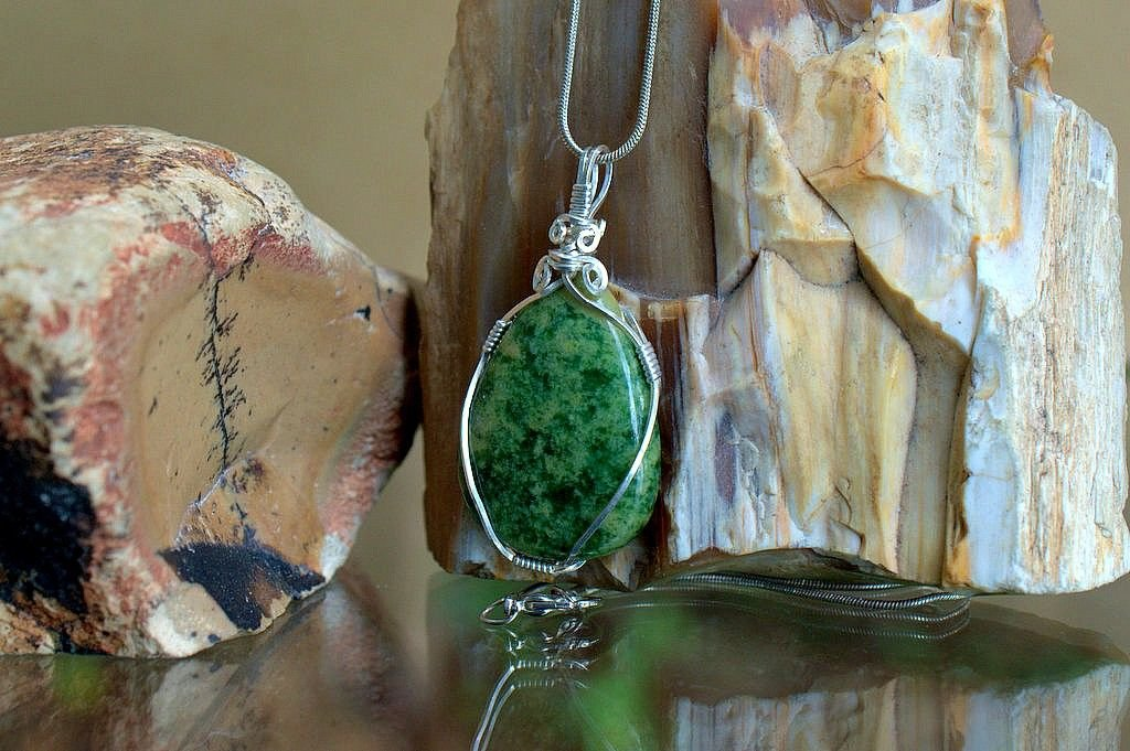 green gemstone pendant with black spot pattern