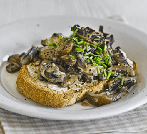 Creamy mustard mushrooms on toast with a glass of juice