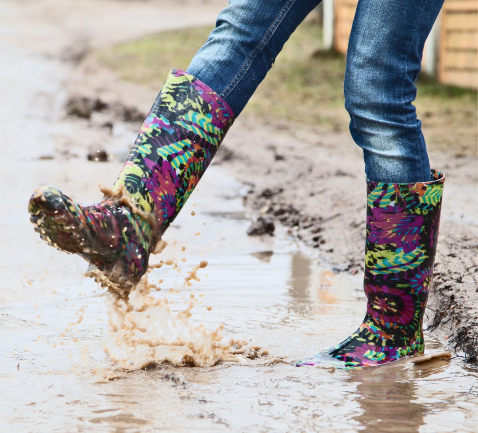 Elizabeth in wellington boots, jumping in a puddle